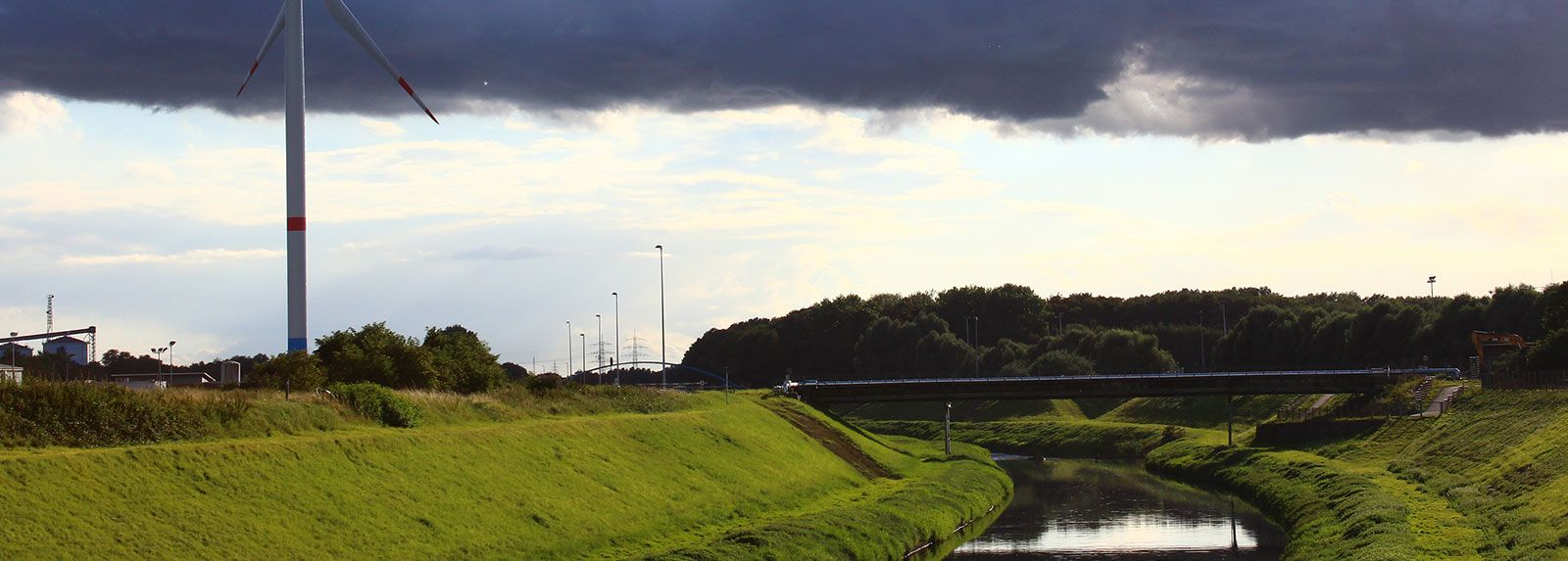 Wind Turbine Beside Canal And Bridge